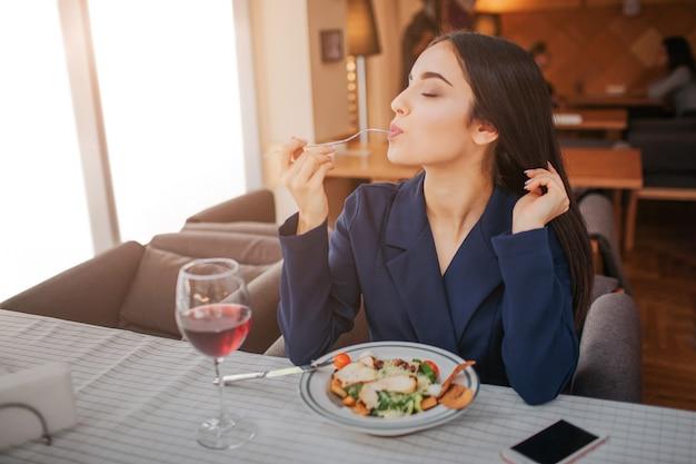 Giovane donna adorabile che gode mangiando alimento in ristorante.
