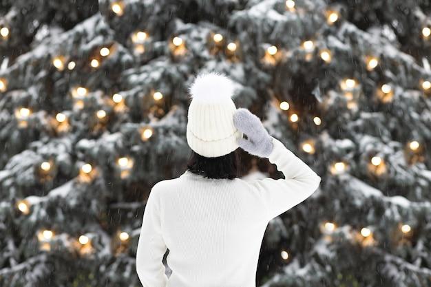 Adorabile giovane donna indossa un maglione e cappello a maglia guardando i pini con la neve decorata con ghirlande