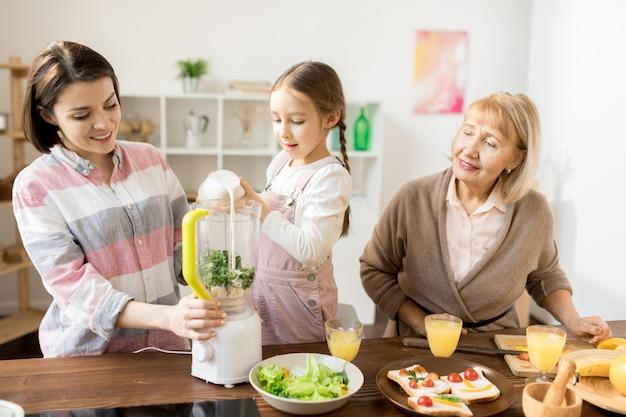 Ragazza adorale che versa latte fresco nel miscelatore elettrico mentre aiuta sua madre a produrre frullato