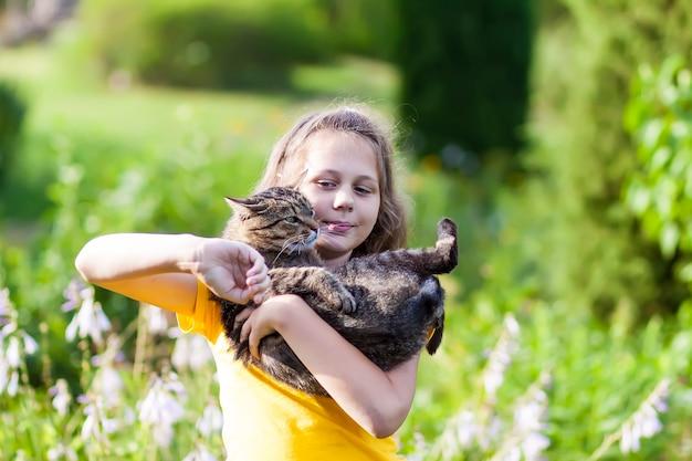 Adorale ragazza in abito giallo che tiene in mano un bel gatto. bambino e animale domestico all'aperto in giornata estiva.