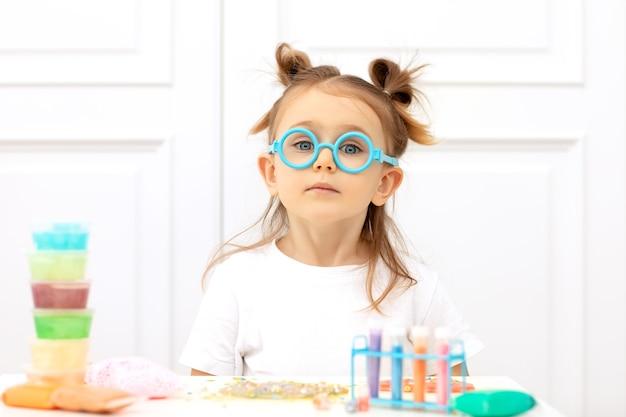Adorabile bambino con una maglietta bianca si siede al tavolo con ingredienti multicolori per esperimenti