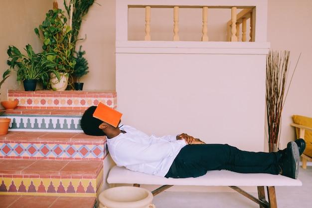 Ragazzo americano dell'adrican che dorme con il libro sul suo fronte