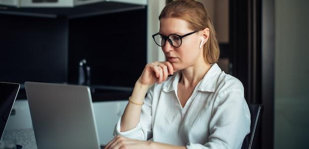 Una donna adulta di 40 anni con gli occhiali e la camicia bianca sta lavorando con il computer portatile in un ufficio a casa. scrittrice positiva. freelance, coworking, lavoro a distanza, lavoro autonomo, lockdown.