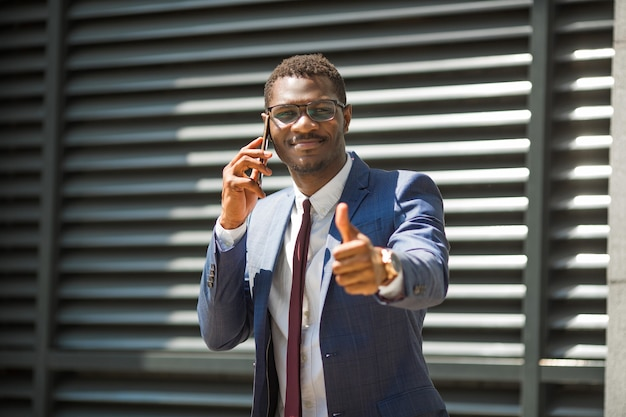 Uomo africano adulto in tuta e occhiali parlando al telefono con un gesto della mano
