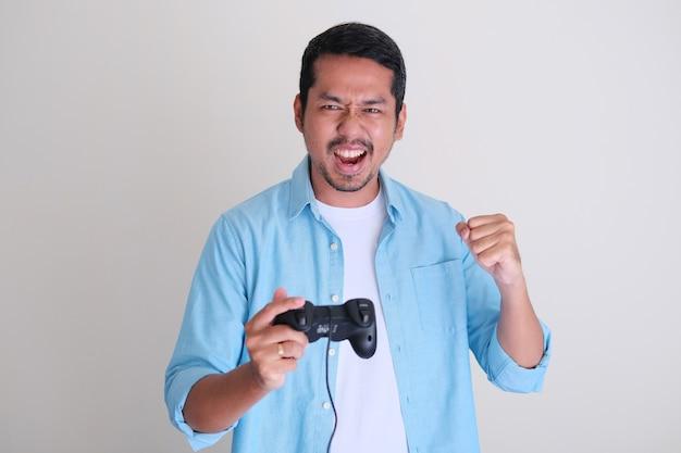 Uomo asiatico adulto che tiene in mano un controller di gioco e mostra un'espressione felice dopo aver vinto il gioco