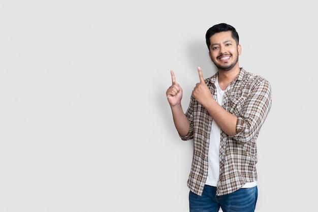Uomo asiatico adulto sopra fondo isolato sorridente allegro che presenta e che indica con il palmo della mano guardando la telecamera.