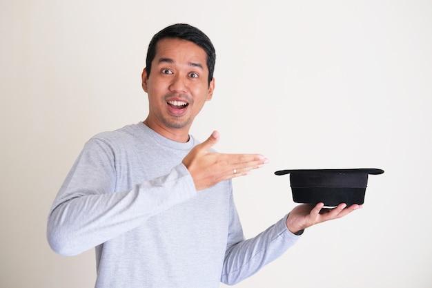 Uomo asiatico adulto che ride mentre tiene in mano un cappello da mago