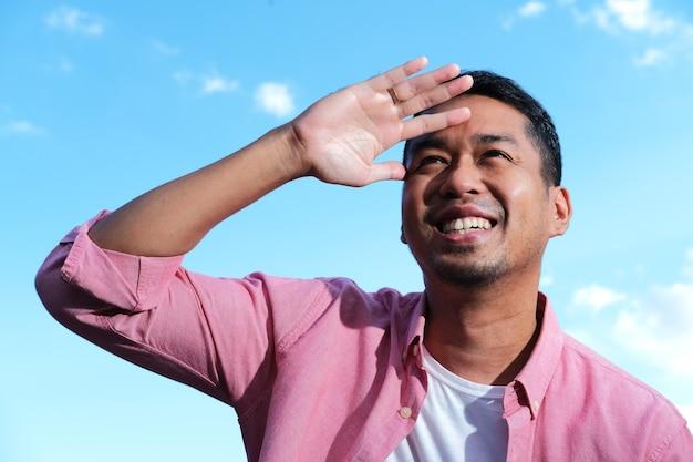 Uomo asiatico adulto che guarda lontano con l'espressione del viso felice sullo sfondo del cielo blu brillante