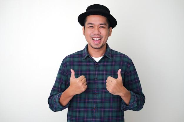 Uomo asiatico adulto che mostra un'espressione eccitata e dà due pollici in su