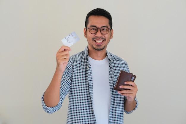 Uomo asiatico adulto che mostra un'espressione felice mentre mostra la sua carta di credito e tiene in mano il portafoglio