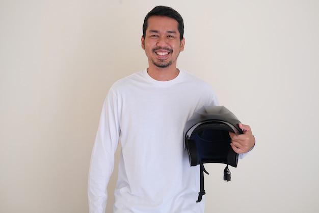Uomo asiatico adulto sorridente amichevole mentre tiene un casco da moto accanto