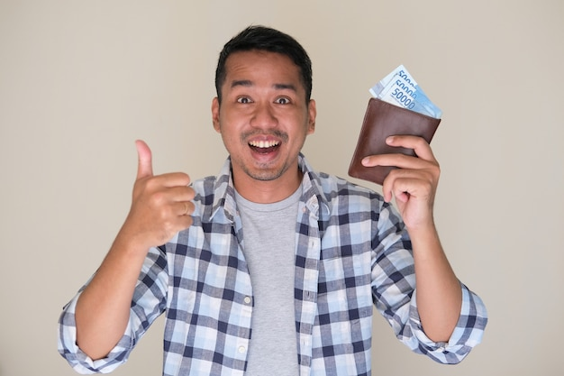 Uomo asiatico adulto che sorride felice mentre dà il pollice in su e mostra soldi di carta nel suo portafoglio