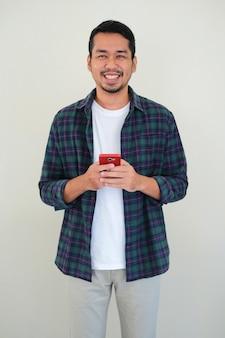 Uomo asiatico adulto che sorride felice mentre tiene in mano un telefono cellulare