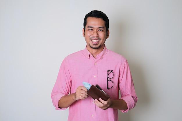 Uomo asiatico adulto che sorride mentre estrae soldi dal portafoglio