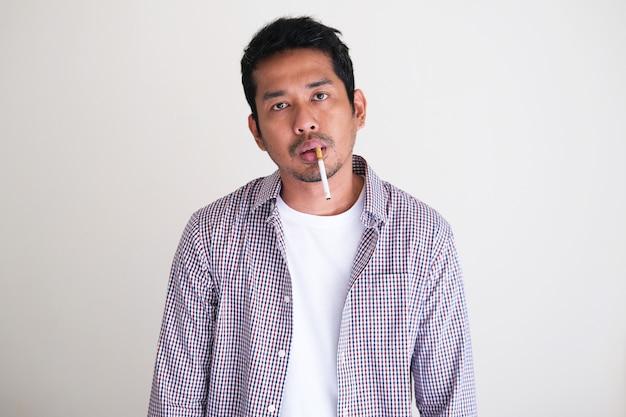 Uomo asiatico adulto che fuma con un'espressione del viso molto disordinata
