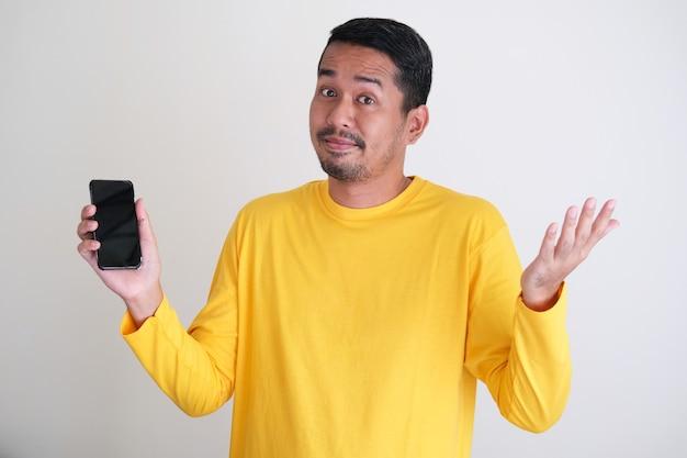 Uomo asiatico adulto che indossa abiti di colore giallo brillante che tiene in mano un telefono cellulare e mostra un gesto confuso