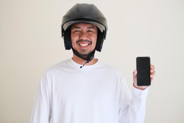 Uomo asiatico adulto che indossa il casco della motocicletta mentre mostra lo schermo del telefono cellulare vuoto