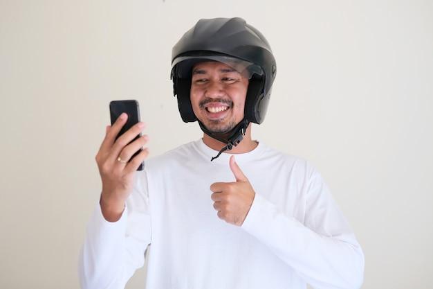 Uomo asiatico adulto che indossa il casco da motociclista che mostra l'espressione del viso felice