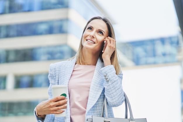 Attraente donna d'affari adulta con smartphone e caffè a piedi in città. foto di alta qualità