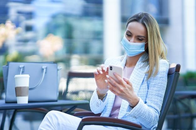 Donna attraente adulta in maschera che utilizza smartphone e si rilassa in città