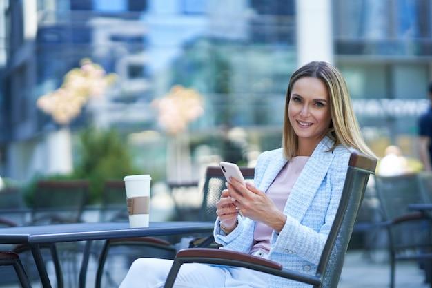 Donna attraente adulta che utilizza smartphone e si rilassa in città