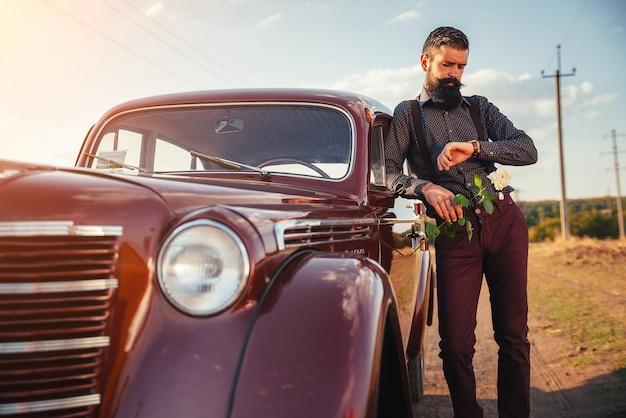 Una bruna barbuta adulta in una camicia, pantaloni con bretelle tiene una rosa bianca in mano vicino a un'auto retrò marrone su una strada di campagna e guarda l'orologio