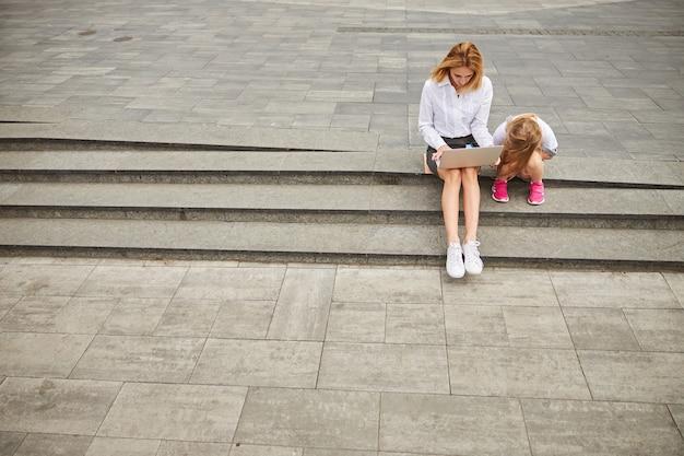 Bella signora adulta che trascorre del tempo all'aria aperta al laptop mentre è seduta sui gradini con la sua piccola bambina