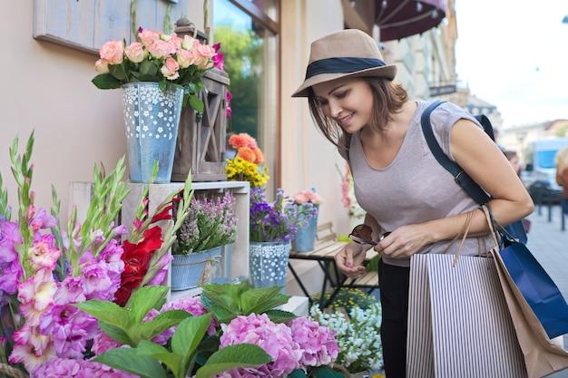 Bella donna sorridente adulta con i sacchetti della spesa che scelgono i fiori al negozio di fiori all'aperto. giorno d'estate, sfondo strada di città
