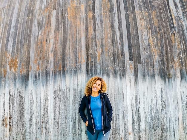 La bella donna adulta posa per un'immagine con la vecchia superficie grigia della parete