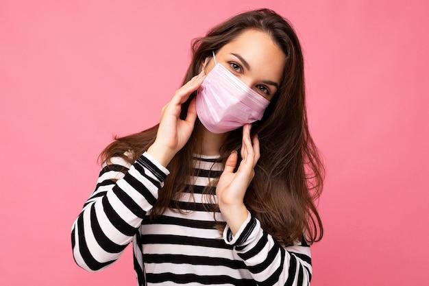 Bella donna adulta in maschera protettiva antivirus riutilizzabile sul viso contro il coronavirus isolato sulla parete di fondo rosa.