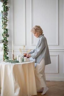Bella donna adulta che serve tavola rotonda festiva con tovaglia bianca