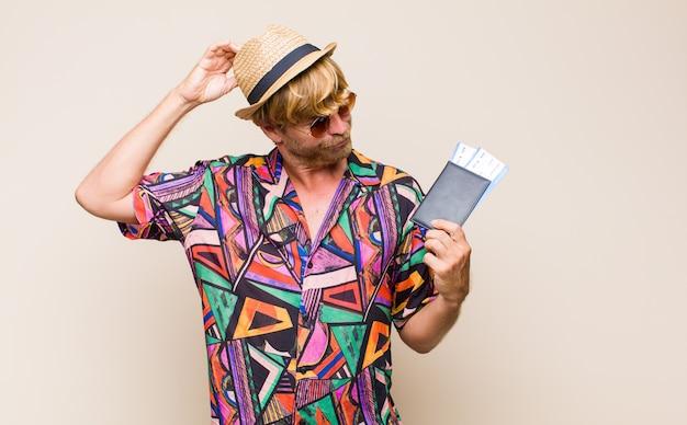 Uomo biondo adulto con un passaporto e biglietti aerei d'imbarco
