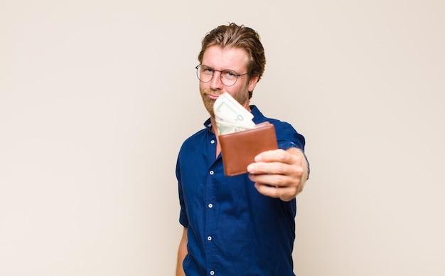 Uomo biondo adulto con un portafoglio e banconote in dollari