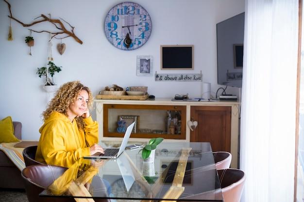 La donna bionda adulta a casa lavora con il computer portatile e la connessione internet