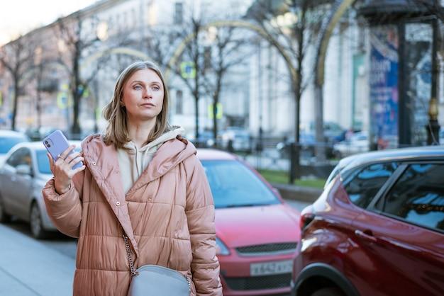 Una donna bionda adulta con i capelli lunghi in un piumino in una strada cittadina in una giornata autunnale la donna ha...