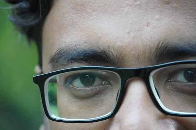 Ragazzo adulto nel parco che si diverte e gioca a guardare gli occhiali