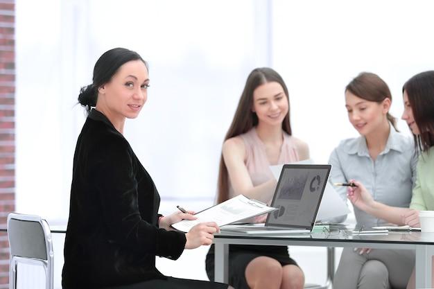 Donna d'affari adulta e gruppo di giovani dipendenti al lavoro scrivania.