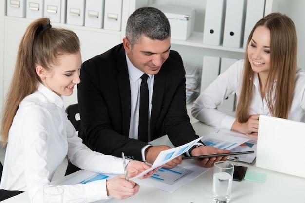 Uomo d'affari adulto che consulta i suoi giovani colleghi femminili durante la riunione d'affari. partner che discutono documenti e idee