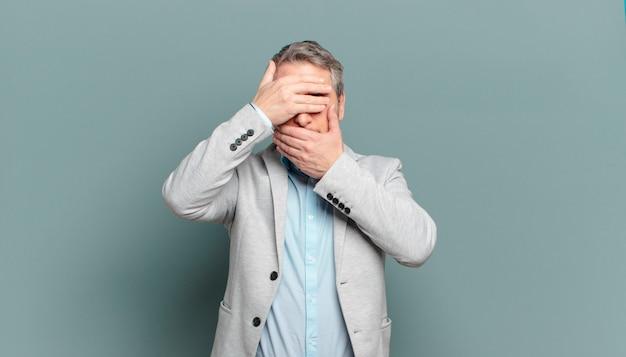 Uomo d'affari adulto che copre il viso con entrambe le mani dicendo no! rifiutare le immagini o vietare le foto
