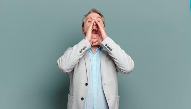 Uomo d'affari adulto che si sente felice, eccitato e positivo, emette un grande grido con le mani vicino alla bocca, chiamando