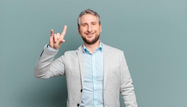 Uomo d'affari adulto che si sente felice, divertente, fiducioso, positivo e ribelle, facendo segno di rock o heavy metal con la mano