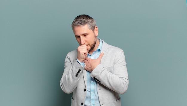 Imprenditore adulto sensazione di malessere con mal di gola e sintomi influenzali, tosse con la bocca coperta