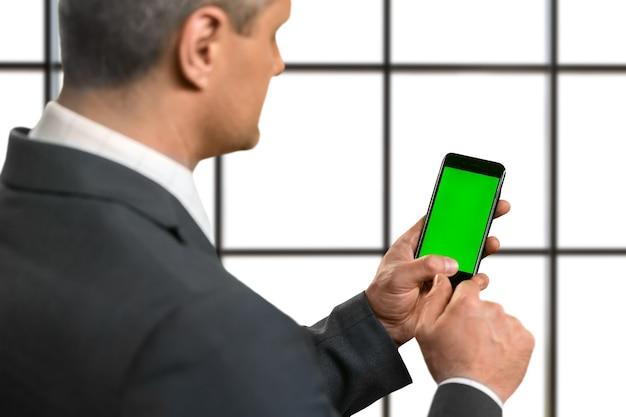 Uomo d'affari adulto che tiene uno smartphone.