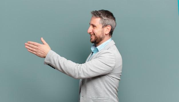 Uomo d'affari adulto sorridente, salutandoti e offrendo una stretta di mano per concludere un affare di successo, concetto di cooperazione