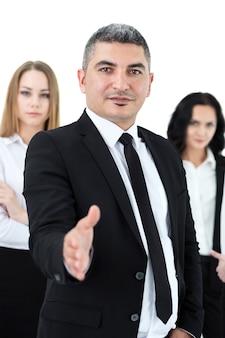 Uomo d'affari adulto in piedi davanti ai suoi colleghi offrendo il suo braccio per la stretta di mano. gruppo di uomini d'affari