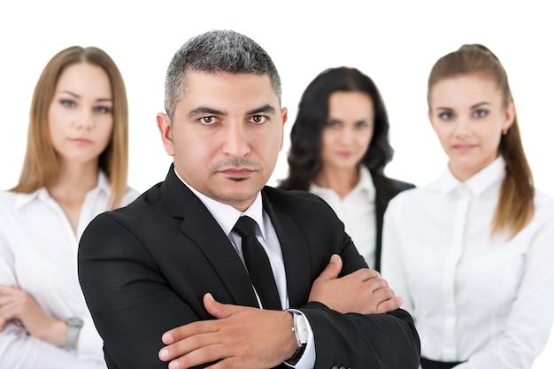 Uomo d'affari adulto in piedi davanti ai suoi colleghi con le braccia incrociate sul petto. gruppo di uomini d'affari team