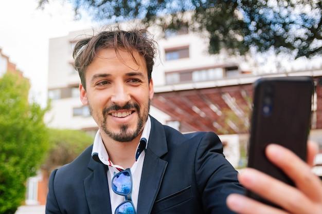 Uomo d'affari adulto che si fa un selfie con il suo smartphone nel parco vicino all'ufficio o al posto di lavoro