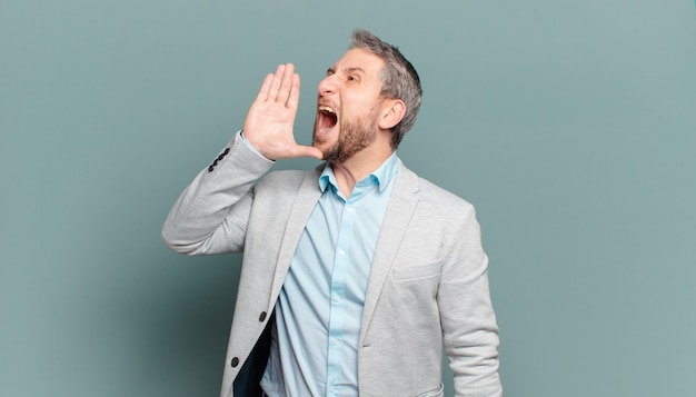 Uomo d'affari adulto che urla ad alta voce e con rabbia per copiare lo spazio sul lato, con la mano vicino alla bocca