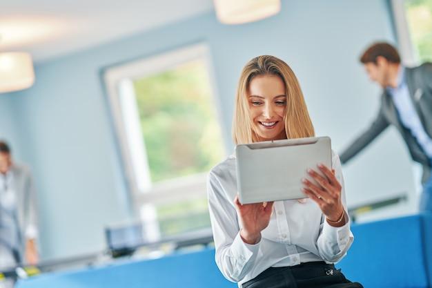 Donna d'affari adulta che utilizza il computer nella sala giochi zona relax donna che gioca a ping pong in background