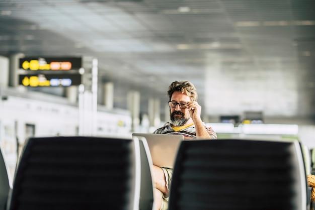 L'uomo caucasico adulto lavora a un computer portatile in attesa del suo volo al cancello dell'aeroporto